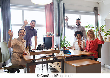 happy creative team waving hands in office - business,...