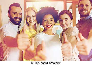happy creative team showing thumbs up in office