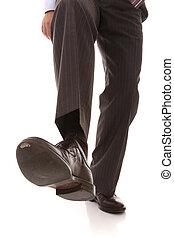shoe and leg of a businessman caution step (selective focus)