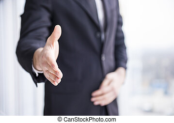Businessman is wearing in suit, handshake to you.