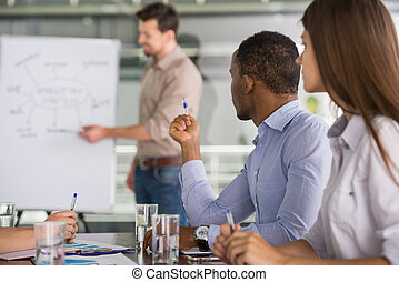 Business - Successful team leader with his team at meeting...