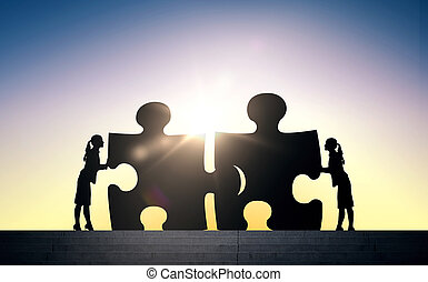 silhouette of two business women connecting puzzle