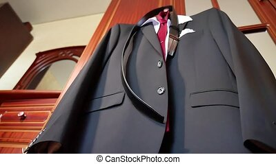 Business suits hanging on a rack. The jacket hangs on the...