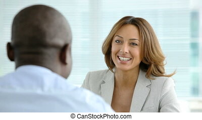 A pretty woman holding a job interview talking to an afro-american man