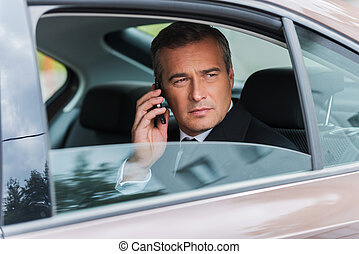 Business talk in car. Confident mature businessman talking on the mobile phone and looking away while sitting on the back seat of a car