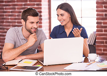 Business talk. Two cheerful young colleagues discussing something while looking at laptop
