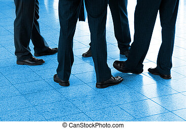 Detail of four businessmen in the circle, blue toned