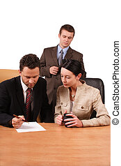 Business team 2 - 3 people reading report at the desk -...