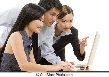 Business Team 8 - An asian business team looking at a laptop...