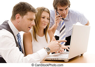 Business Team - A business team of three works on a laptop...
