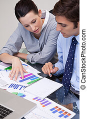 Business team analyzing charts - Young business team...