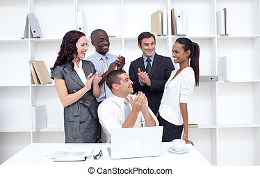 Business team applauding a collegue in office