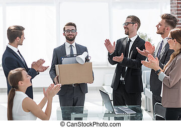 business team applauding at a meeting with the new employee.