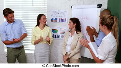 Business team applauding colleague