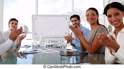 Business team applauding the camera at meeting in the office