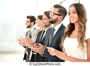 business team applauding to someone while standing in the office.