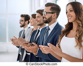 business team applauding to someone while standing in the office