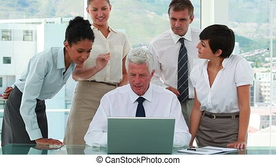 Business team around their boss watching a laptop screen