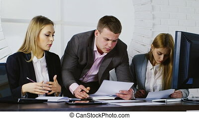 Business team at work, a man and two women working with documents