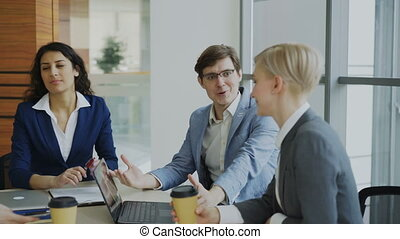 Business team chatting while sitting in modern office indoors during coffee break