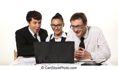 Business team cheerfully talking, very happy news. laptop in front of them. Slow motion