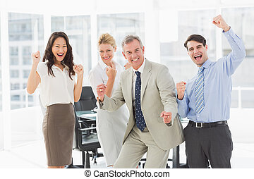 Business team cheering at the camera