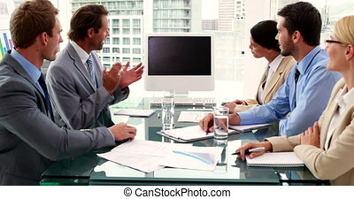Business team clapping a screen - Business team clapping a...
