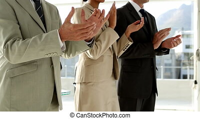 Business team clapping in office in front of large window