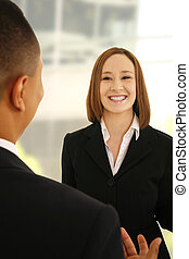 two business people talking in office environment as if discussing a business plan