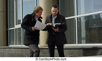 Business team discussing papers outdoor