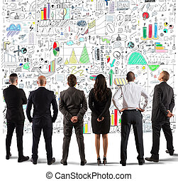 Business team drawing a new complex project on wall