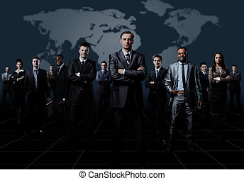 business team formed of young businessmen standing over a dark background.