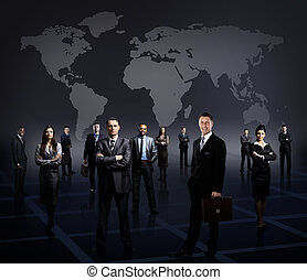 business team formed of young businessmen standing over a dark background