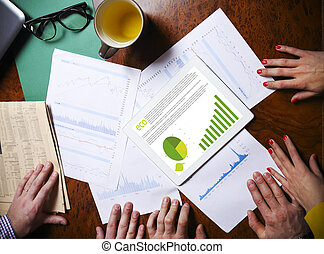 Business team hands at work with financial reports and a...