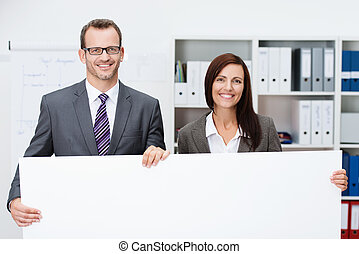 Business team holding a blank white sign with a smiling...