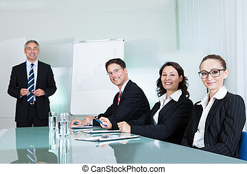 Smiling successful business team holding a meeting sitting around a white glass topped table with one executive