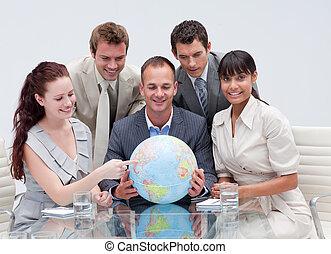 Business team holding a terrestrial globe. Worldwide business