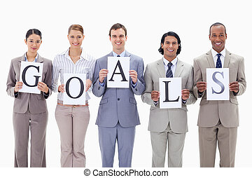 Business team holding the letters of GOALS against white...
