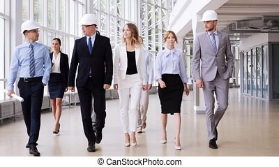 business team in helmets with blueprint at office 53