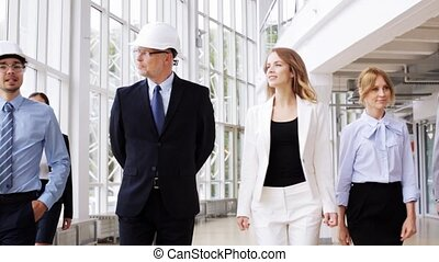 business team in helmets with blueprint at office 55