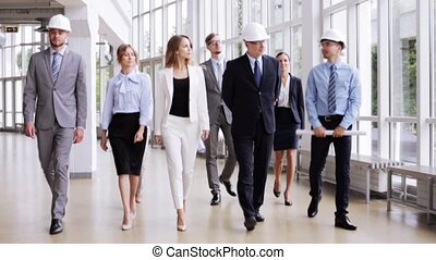 business team in helmets with blueprint at office 60
