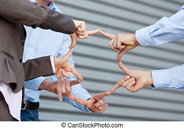 Business team Joining Fingers Against Shutter - Closeup of...