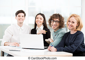 Business team looking at camera while working with laptop