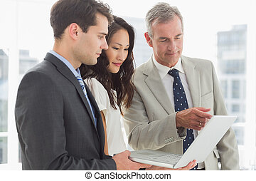 Business team looking at laptop together