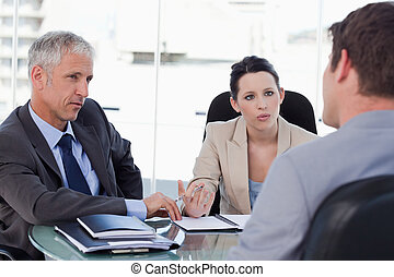 Business team negotiating with a customer in a meeting room