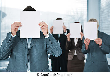 Business team of four holding blank paper
