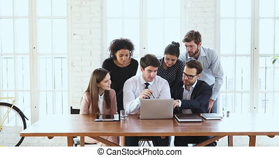 Business team of six brainstorm gather in office with laptop
