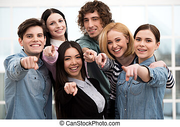 Business team pointing and looking at camera in office
