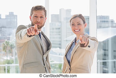 Business team pointing at camera