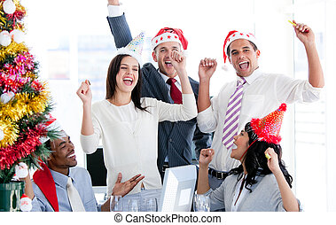 Business team punching the air to celebrate christmas in the...